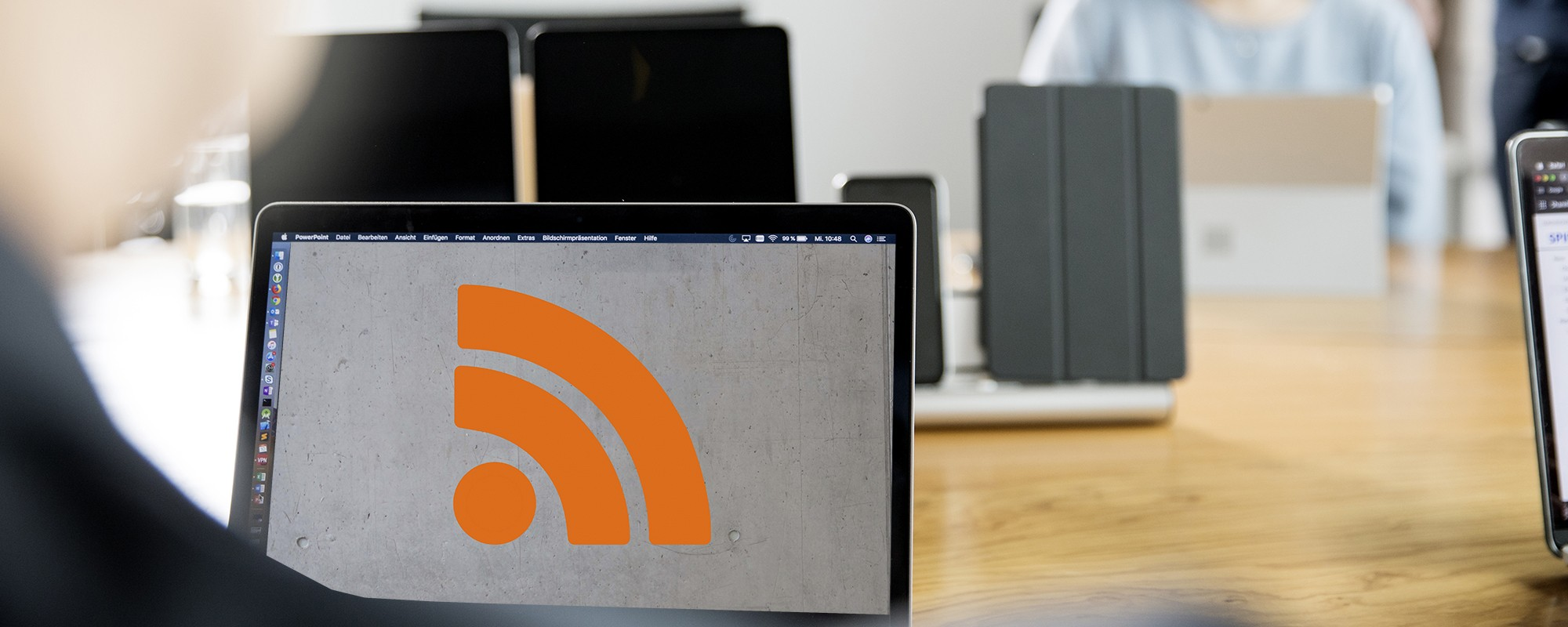 Meetingsituation mit Blick auf einen Mac-Monitor, auf dem ein RSS-Symbol zu sehen ist