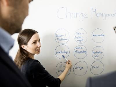 Eine Frau deutet am Whiteboard auf das Wort Leadership