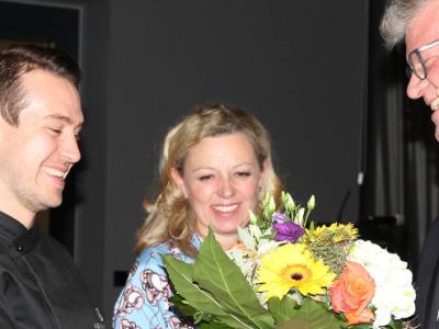 Drei Menschen, wobei der Frau vermuttlich ein Blumenstrauss überreicht wird