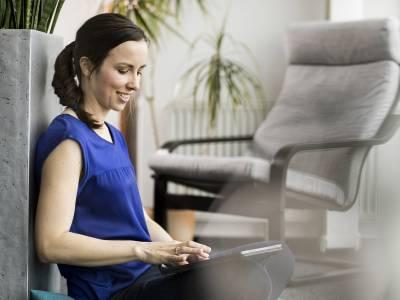Eine Frau, die am Boden sitzt und mit dem iPad arbeitet
