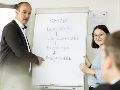 Ein Mann und eine Frau erklären etwas an einen Flipchart