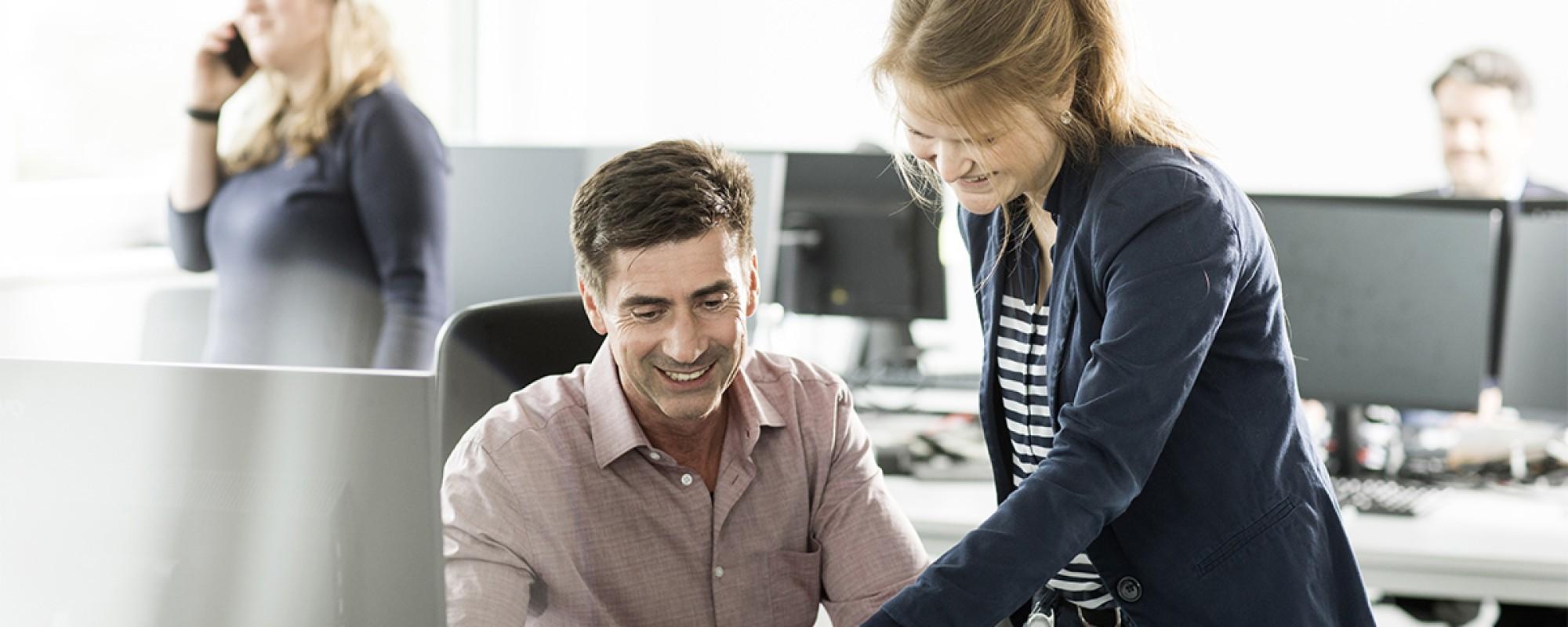 Ein Mann und eine Frau welche zusammen an einem iPad arbeiten. Im Hintergrund arbeiten zwei Menschen.