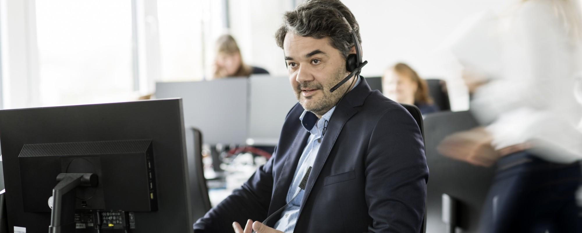 Ein Mann in einem voll besetzten Büro. Er sitzt mit einem Headset an seinem Schreibtisch und führt ein Telefonat.